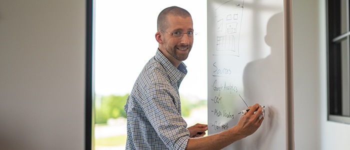Ryan-Eme-at-markerboard-smiling